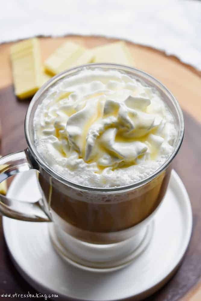 White chocolate mocha topped with whipped cream and white chocolate syrup in a clear mug on top of a wooden platter