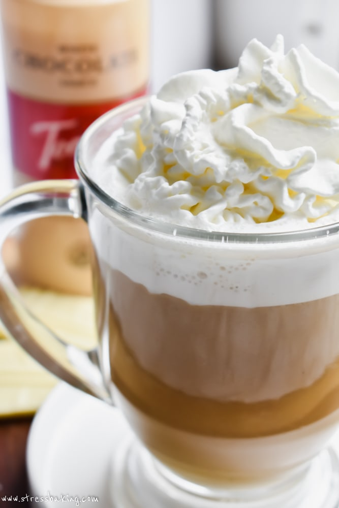 Side shot of a white chocolate mocha with whipped cream and white chocolate syrup in a clear mug