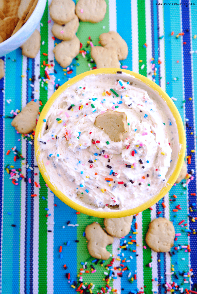Yellow bowl full of funfetti dip topped with sprinkles on a colorful striped placemat with animal crackers