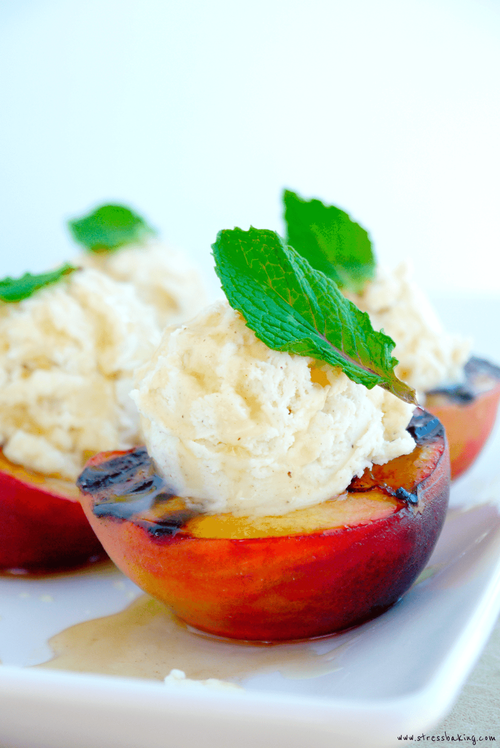Grilled Peaches with Cinnamon Mascarpone Whipped Cream & Honey: A sophisticated looking summer dessert that is easy, colorful and packed with flavor! Soft, juicy grilled peaches are complemented by cinnamon mascarpone whipped cream and drizzled with raw wildflower honey. | stressbaking.com @stressbaking #stressbaking #peachesandcream #grillingseason #summer #peachesncream #fruit #recipe