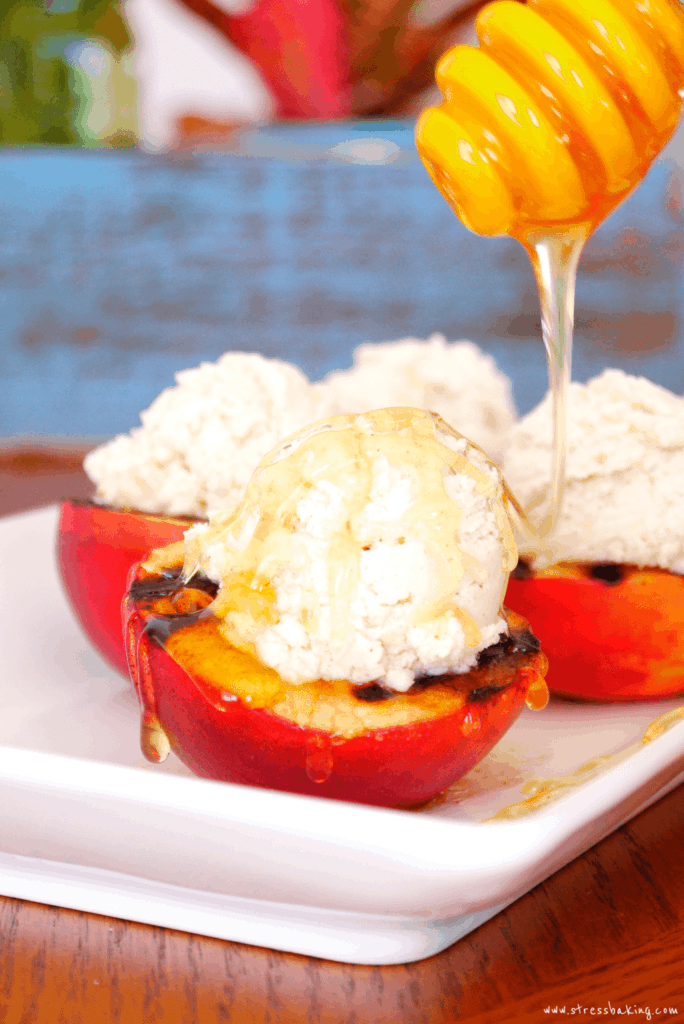 Grilled Peaches with Cinnamon Mascarpone Whipped Cream and Honey: A sophisticated looking summer dessert that is easy, colorful and packed with flavor! Soft, juicy grilled peaches are complemented by cinnamon mascarpone whipped cream and drizzled with raw wildflower honey. | stressbaking.com