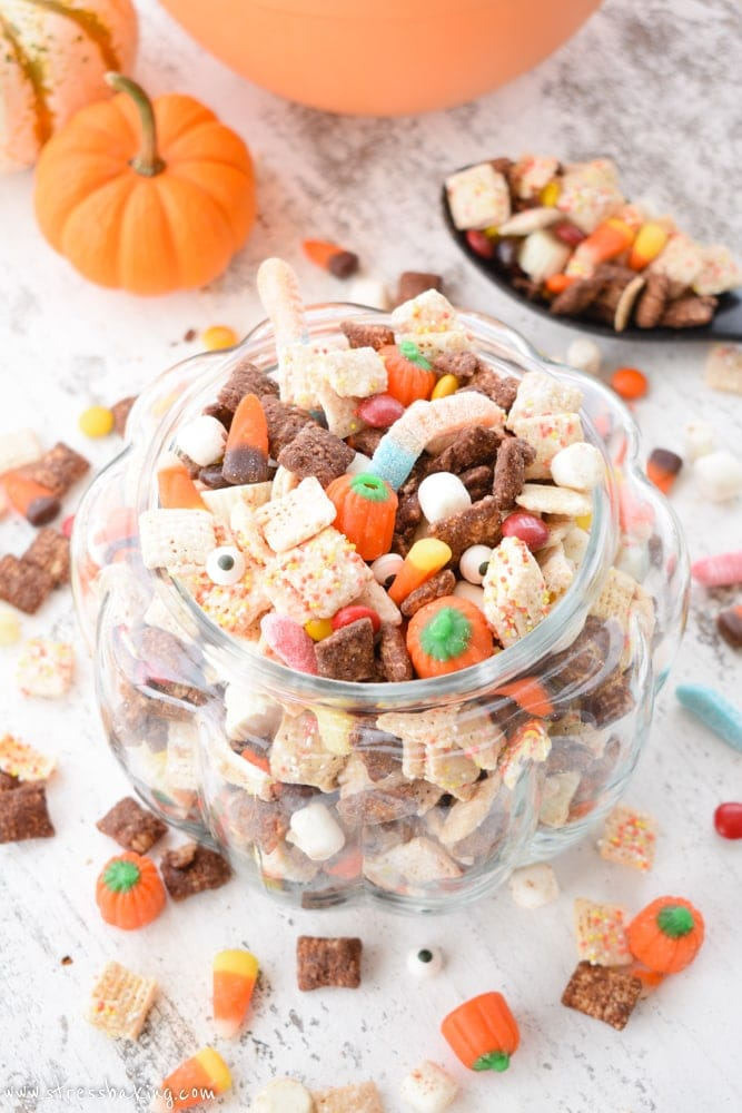 Colorful Halloween puppy chow in a glass pumpkin on a white wooden background