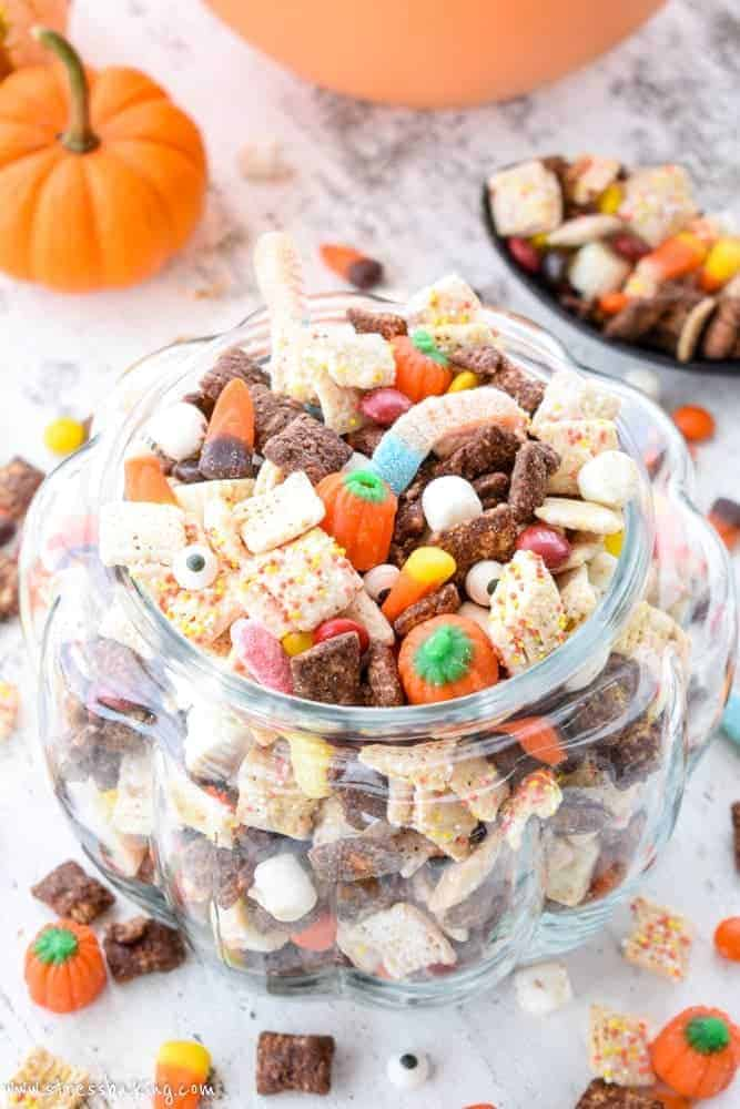 Halloween Puppy Chow: Whether you call it puppy chow or muddy buddies, the addition of Halloween candy and autumn colors turn this into the perfect festive party snack! | stressbaking.com