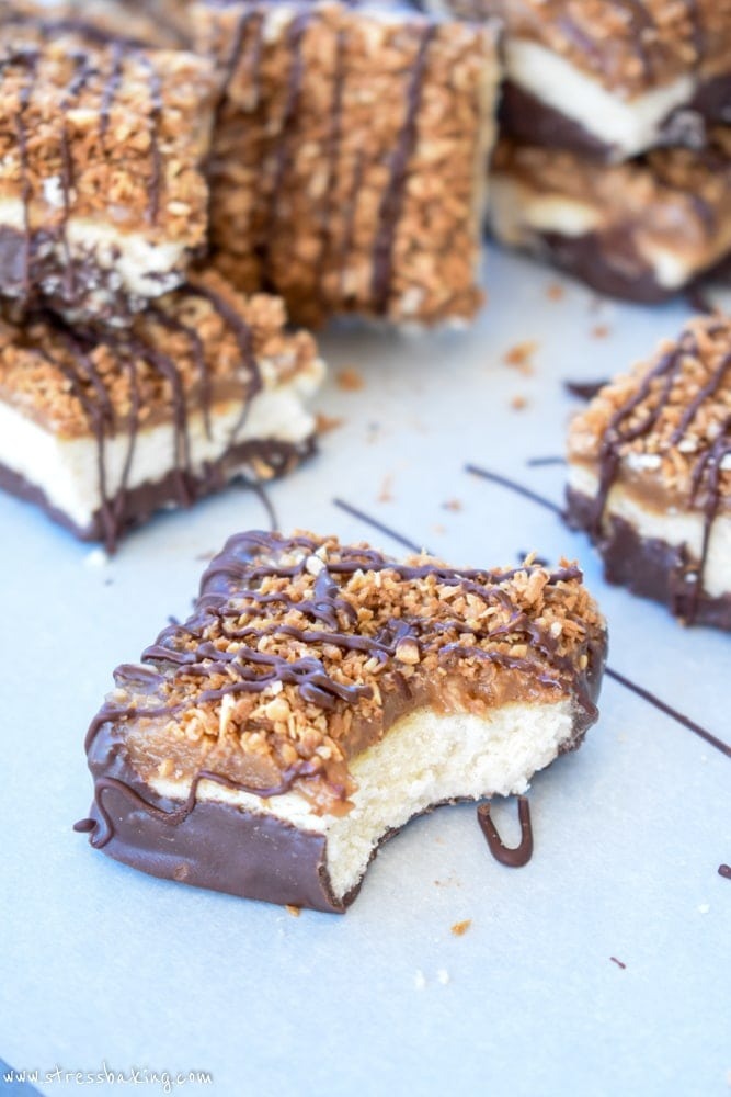 Paleo Samoa Bars: Soft shortbread, gooey caramel, and toasted coconut are dipped in chocolate and topped with a chocolate drizzle! | stressbaking.com