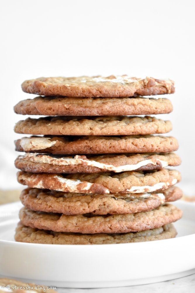Closeup side shot of a stack of peanut butter cookies with marshmallow swirls on a white plate