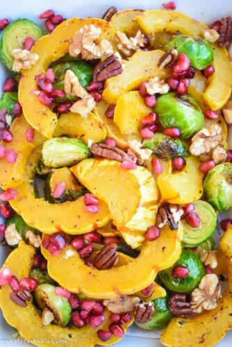 Roasted Delicata Squash and Brussels Sprouts: A fall side dish that will brighten any meal! Roasted delicata squash and brussels sprouts are topped with pomegranate arils for gorgeous pops of color. | stressbaking.com