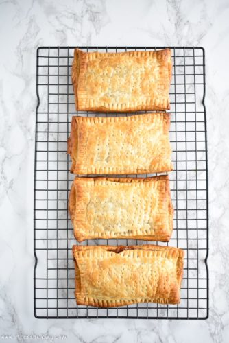 Homemade Apple Cinnamon Toaster Strudel: Nostalgia at its best! Puff pastry envelops warm a warm apple cinnamon filling and is topped with a hearty vanilla cream cheese drizzle. | stressbaking.com