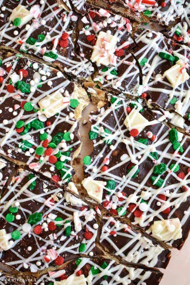 Christmas Crack: Warning: This is SUPER addictive! Saltines are covered with an easy caramel sauce, two types of chocolate, crushed and chopped peppermint, and assorted holiday sprinkles. This is absolute holiday treat perfection. | stressbaking.com #christmasdessert #christmastreat #holidaydessert #holidaytreat