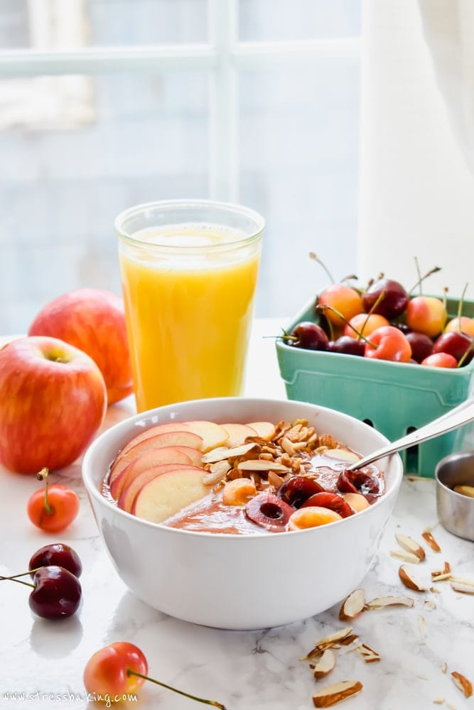 Apple Cheery Smoothie Bowl on a table with fresh fruit and orange juice