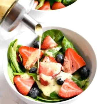 Lemon poppy seed dressing poured on a strawberry spinach salad