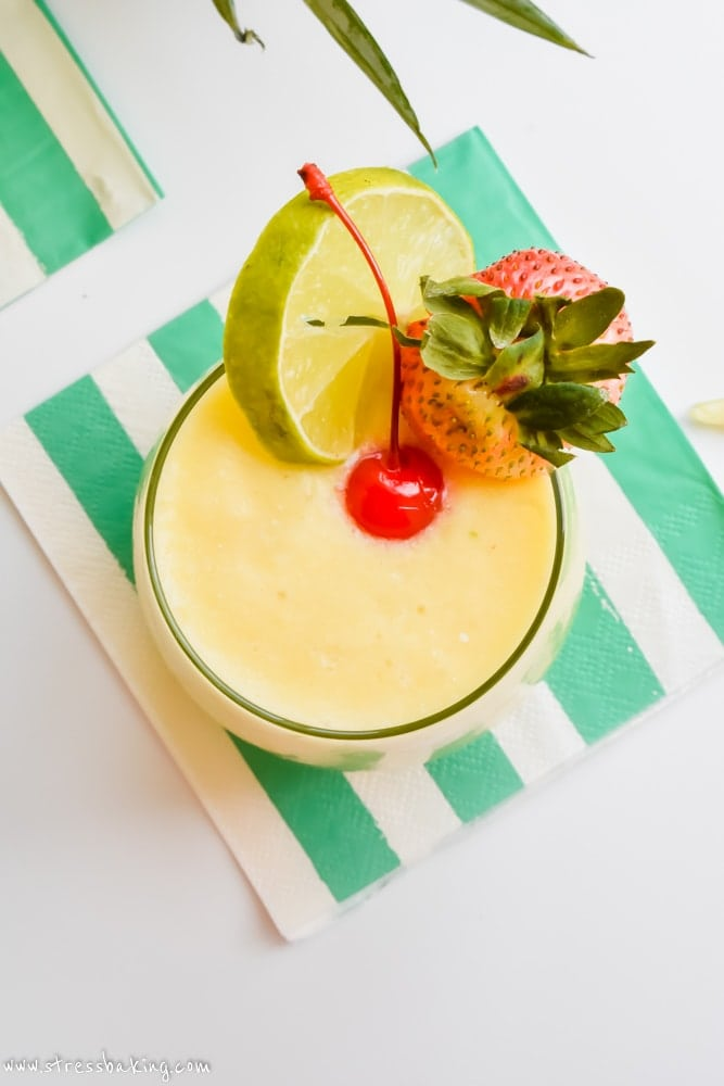 Pineapple cooler summer cocktail with lime, strawberry and a maraschino cherry on a napkin
