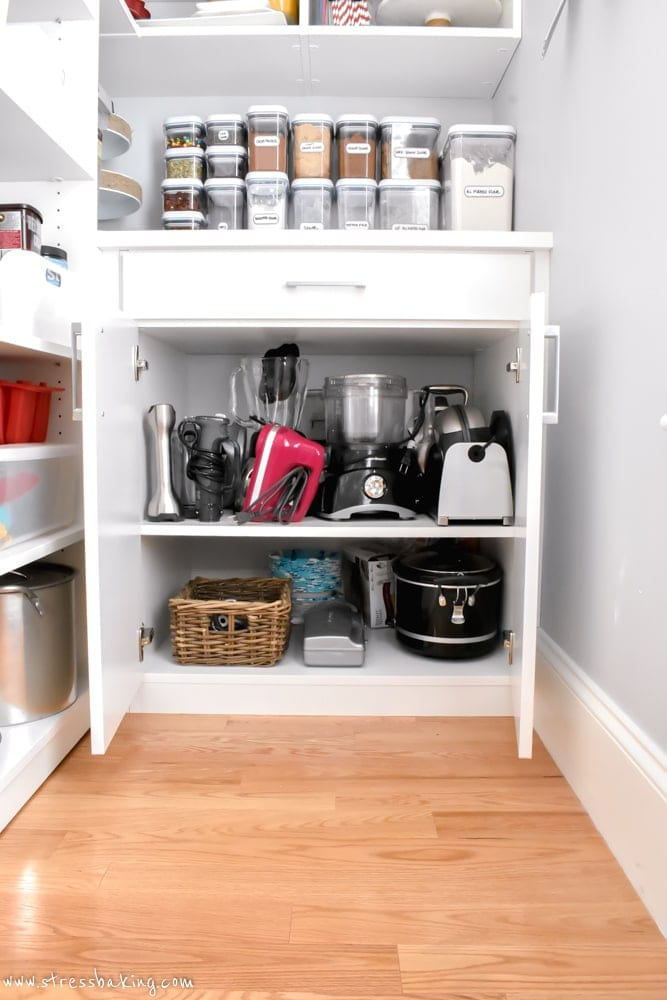 California Closets White pantry cabinet holding kitchen appliances