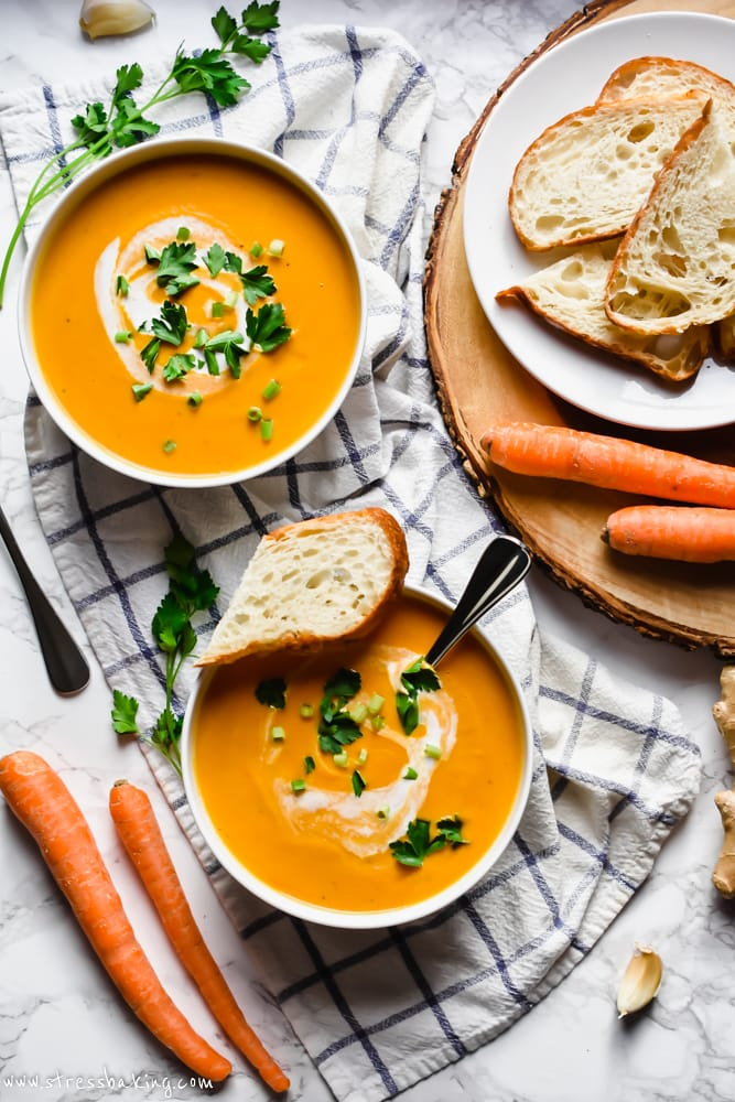 Overhead shot of two bowls of carrot ginger soup topped with swirls of coconut milk, scallions and freshly chopped parsley next to slices of crusty bread