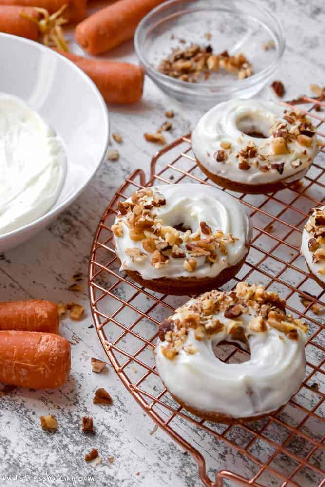 Carrot cake donuts topped with cream cheese icing and chopped nuts