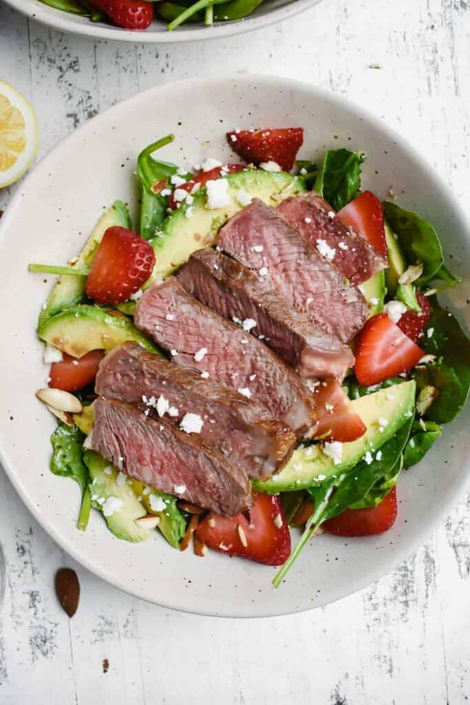spinach salad with strawberries, avocado and steak in a white bowl