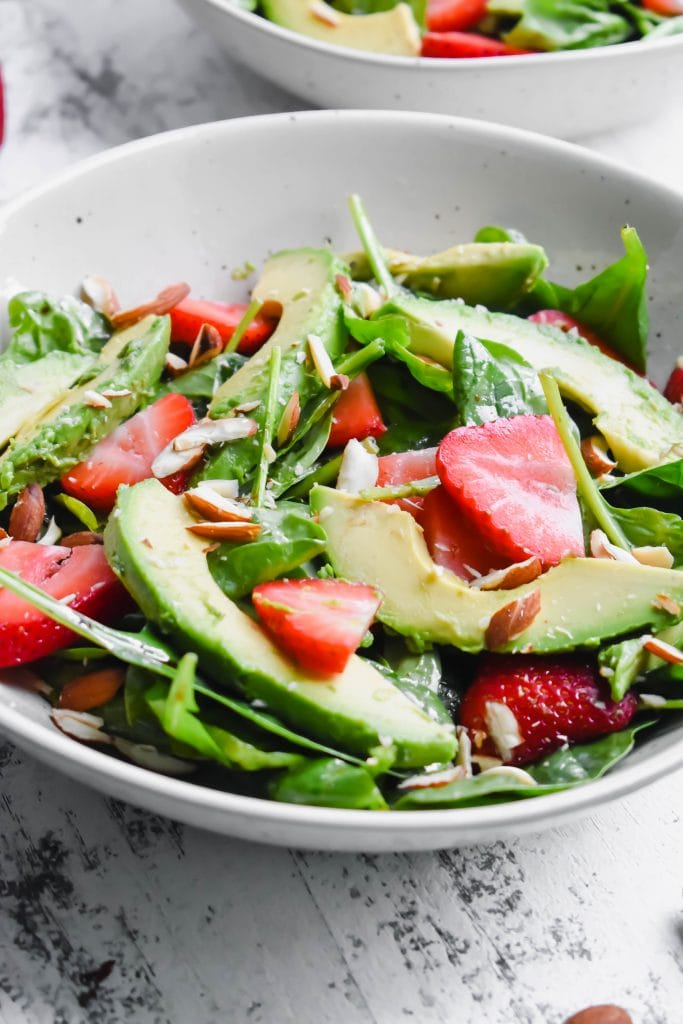 spinach salad with strawberries, avocado in a white bowl