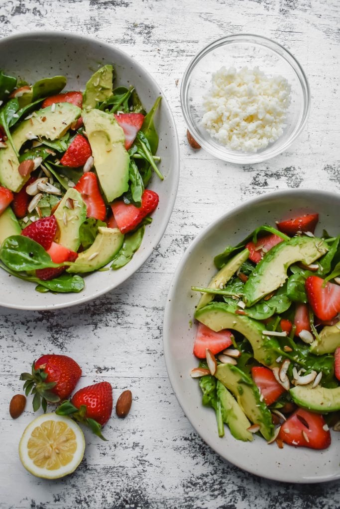 spinach salad with strawberries, avocado in white bowls