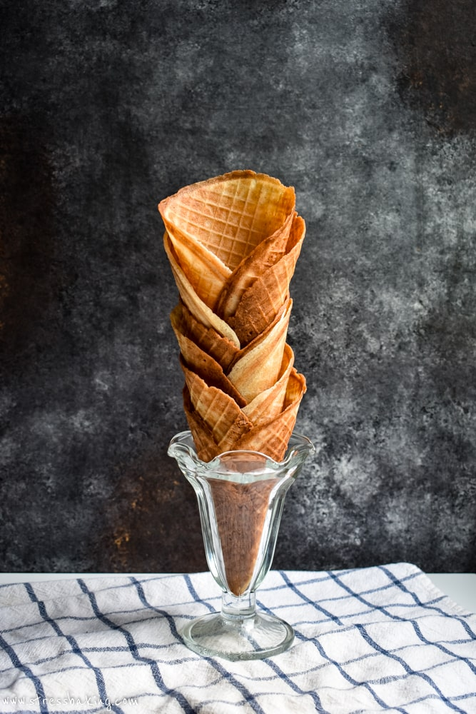 Waffle cones stacked in a vintage glass ice cream dish against a dark background
