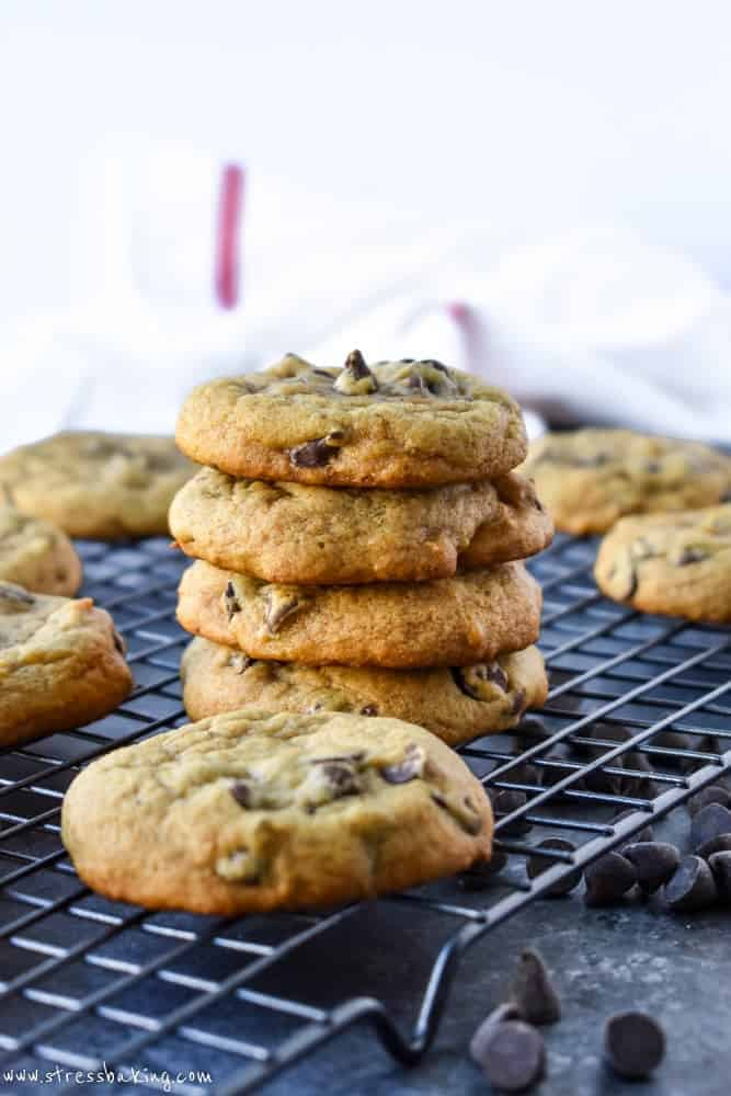 Side shot of a stack of chewy pumpkin chocolate chip cookies on a wire rack and dark background