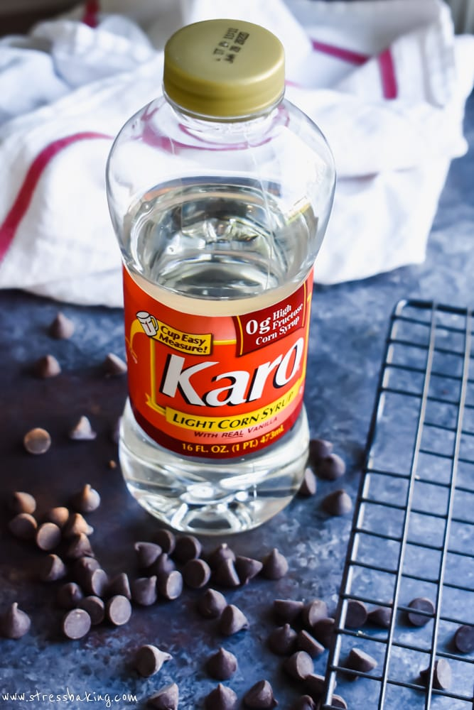 A bottle of Karo® Corn Syrup on a dark background surrounded by loose chocolate chips
