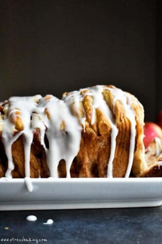 Side shot of white icing dripping down the side of a golden brown loaf of monkey bread